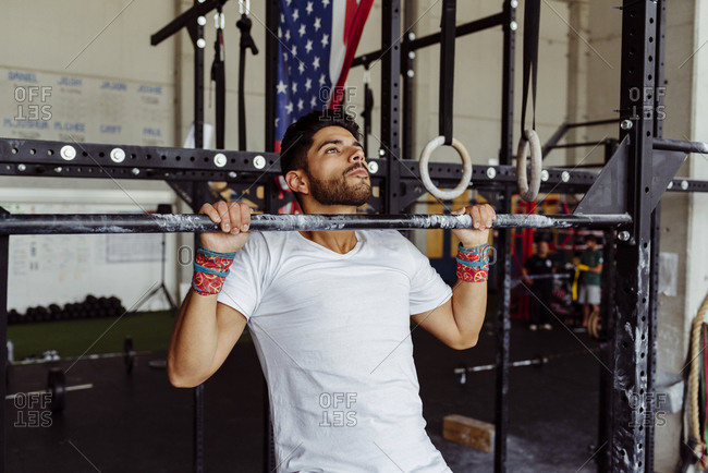 Handsome latin man doing push-ups on the bar in the gym