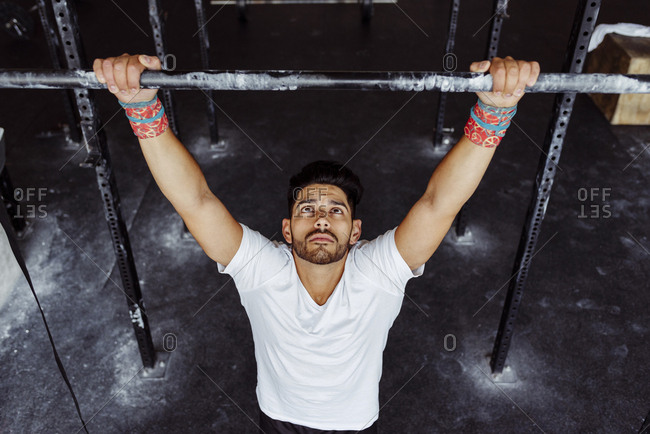 Handsome latin man from above looking at the push-up bar