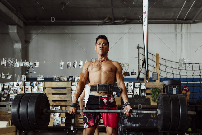 Handsome and strong latin man lifting a heavy weight