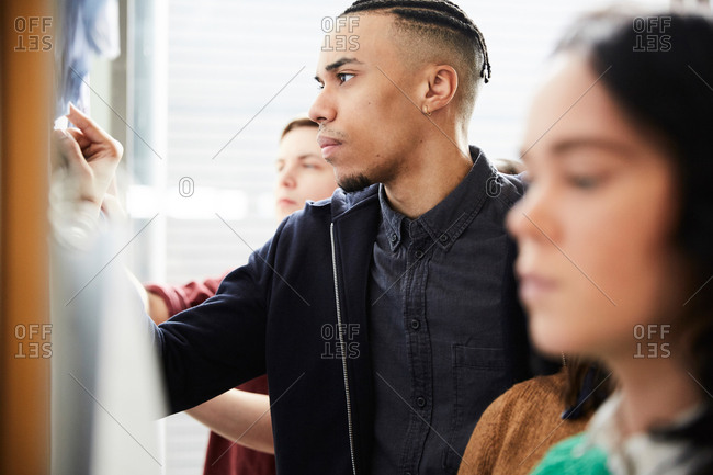 Young man checking test results on bulletin board while standing with friends at university