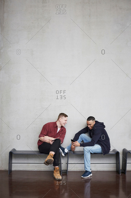 Full length of happy male students with technologies sitting on bench against wall in university