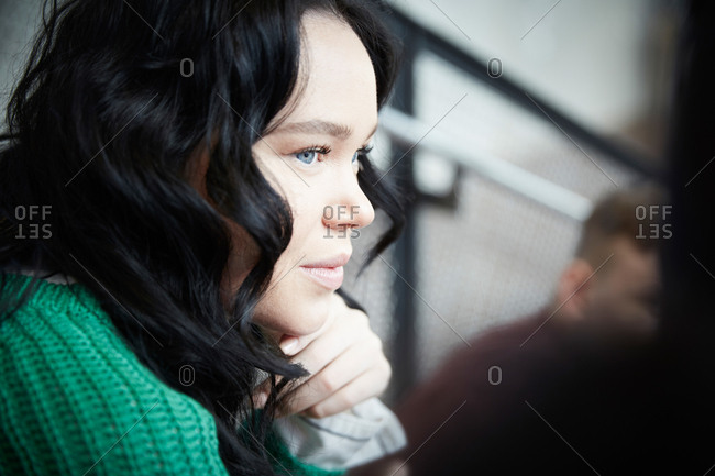 Close-up of young woman with black hair looking away in university