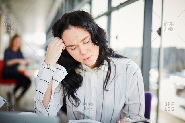 Close-up of stressed female student studying in university cafeteria