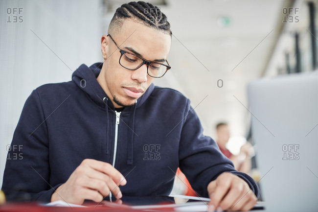 Serious male university student using digital tablet while sitting at table in cafeteria
