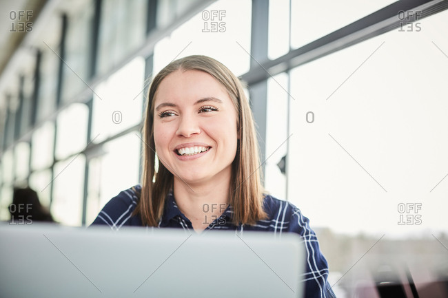 Close-up of smiling university student looking away while sitting at cafeteria