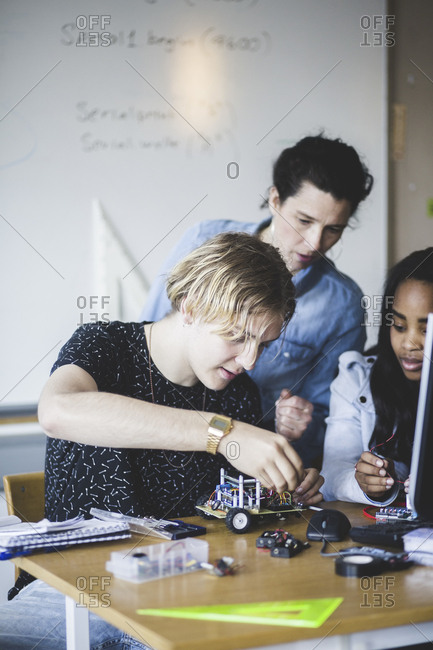 Mature female teacher looking at students preparing toy car on desk in classroom