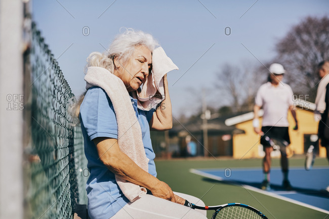 Exhausted senior woman wiping face with towel while sitting at tennis court