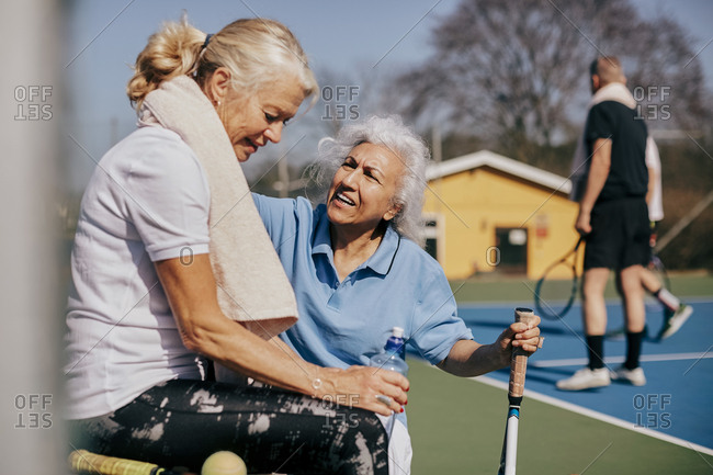 Senior woman talking to tired friend at tennis court
