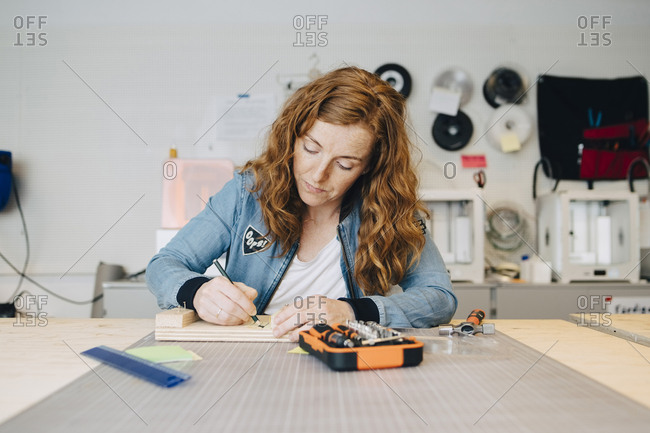 Confident redhead female engineer writing on wood at workbench in creative office