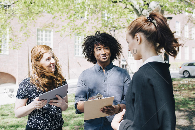 Confident businesswoman discussing with multi-ethnic colleagues while standing outdoors