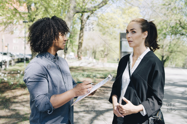 Confident businessman discussing with female colleague while standing on road