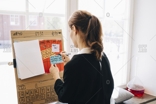 Rear view of businesswoman writing strategy on placard against window at creative office