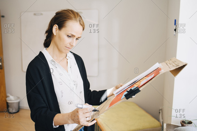 Confident businesswoman writing strategy on placard at creative office