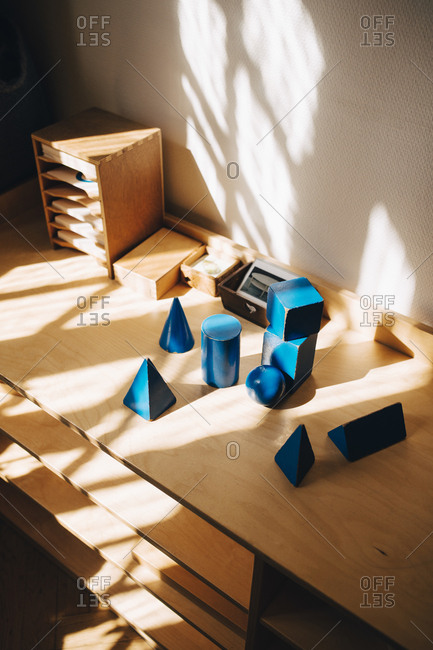 High angle view of toys on wooden table by wall in preschool classroom