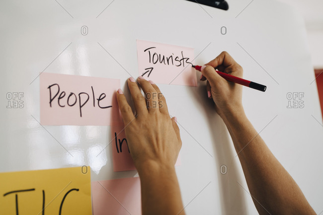 Hands of businesswoman writing on whiteboard while planning at creative office
