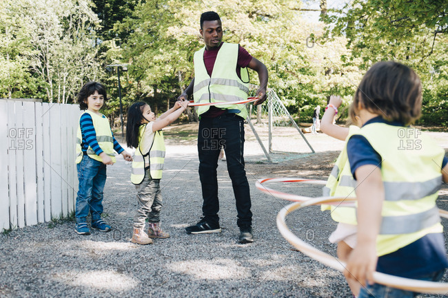 Male teacher and students playing with plastic hoops in playground