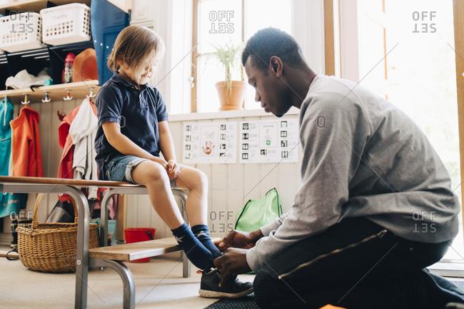 Side view of male teacher helping boy in wearing shoe at kindergarten