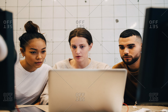 Young multi-ethnic computer hackers looking at laptop against wall in office