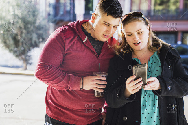 Young woman using mobile phone while man holding disposable cup in city