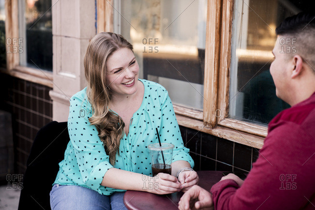Smiling woman talking with boyfriend at sidewalk cafe in city