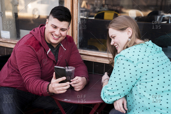 Smiling man showing mobile phone to girlfriend at sidewalk cafe in city