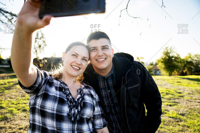 Smiling couple taking selfie with smartphone in park