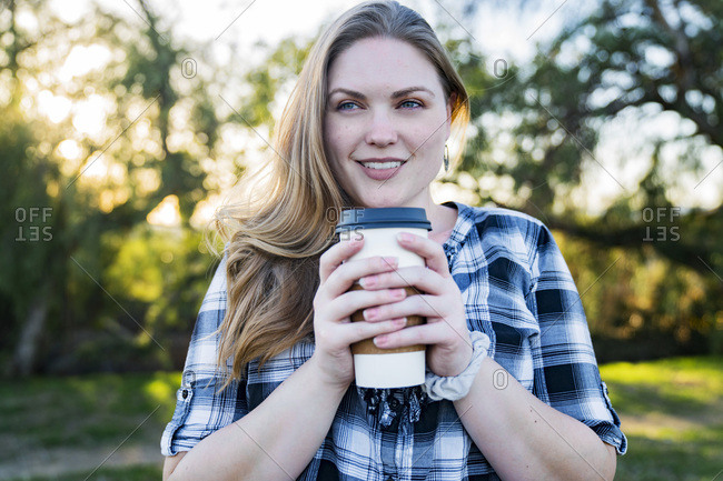 Beautiful woman holding disposable coffee cup in park