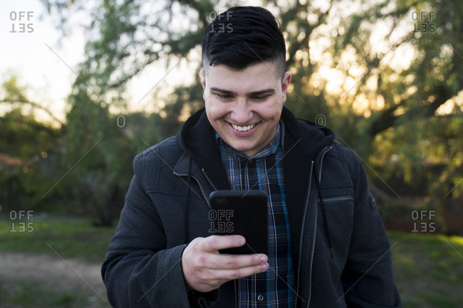 Smiling young man wearing jacket while using smartphone in park