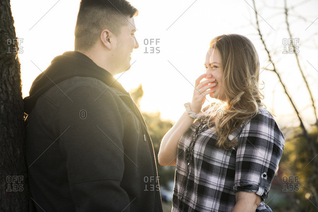 Young man talking while cheerful woman covering mouth in park