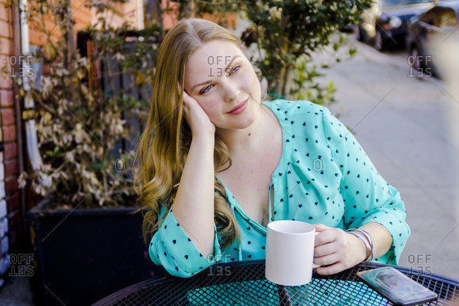 Thoughtful young woman with coffee cup sitting at sidewalk cafe in city