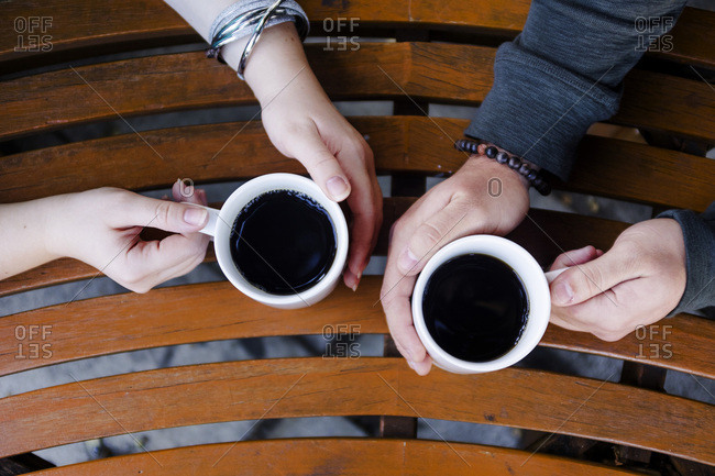 Close-up of couple's hands holding coffee cups at table