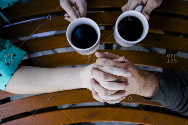 Close-up of couple with coffee cups holding hands at table
