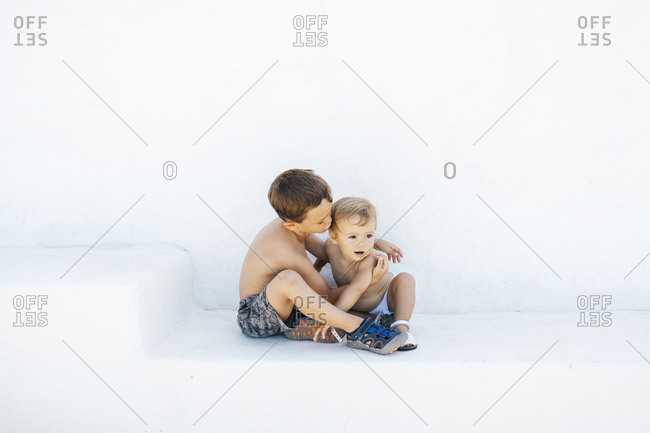 Little boy embracing adorable infant brother sitting on white steps