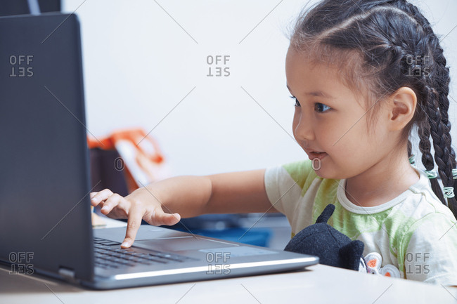 Cute girl using laptop with video games