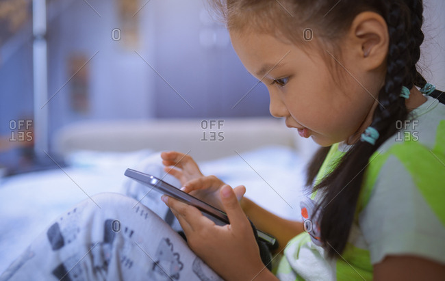 Serious 4-5 years girl using smartphone at home