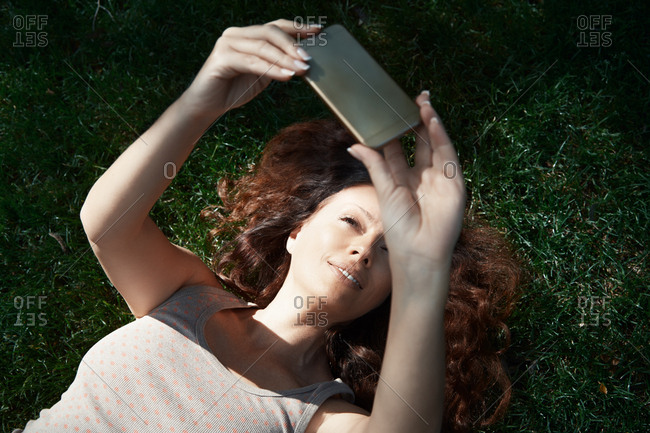 Woman laying on grass and making selfie