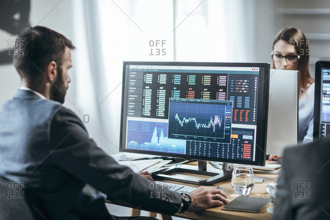 Businesspeople working with finance forecasts on their computers.