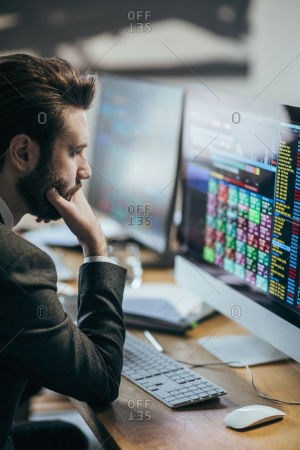 Financial broker analyzing stock market on his computer.