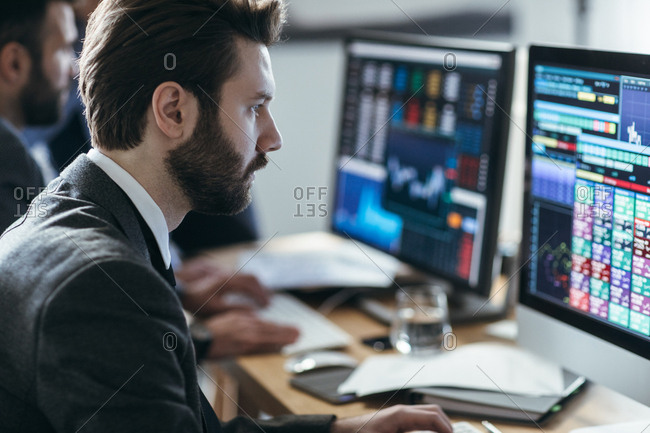 Man broker analyzing chart and stock market performance forecast on his computer.