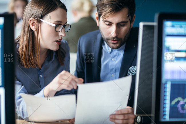 Businessman and businesswoman reading a document together at their office.