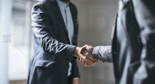 Two cropped businessmen handshaking.