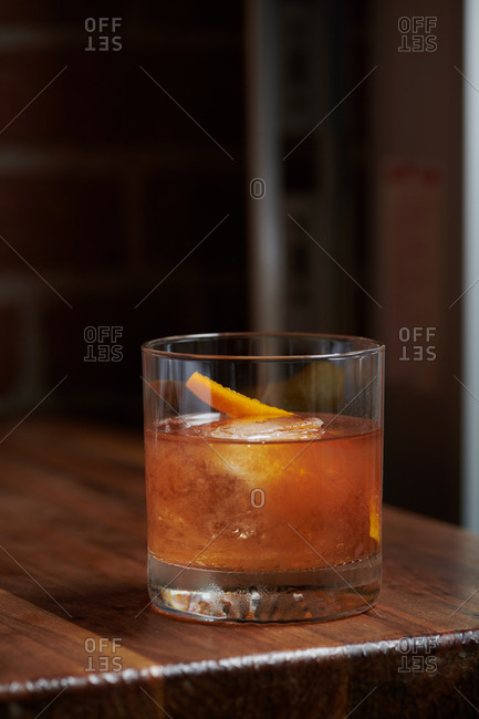 An old fashioned cocktail sits on a wooden table in a tapas style restaurant with a twist of orange peel garnishing the rocks glass with a single ice cube inside. The drink consists of rye whiskey, fig puree, angosturia, and old fashioned bitters.