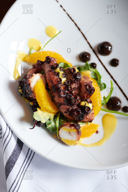 Octopus tapas style dish with black garlic sauce, carrot vinaigrette, orange and greens with a bold presentation.