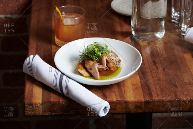 A dish of quail and trumpet mushroom tapas served with a poblano puree and sage jus with a glass of water in the background.
