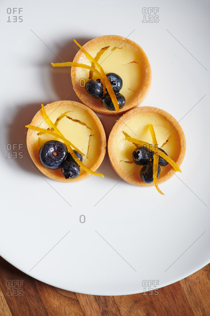 Three Lemon Tartlets served on a white plate with blueberries and candied orange peels for dessert in a Tapas style restaurant.