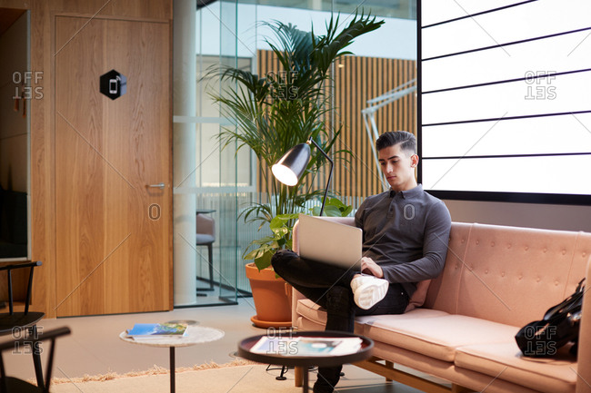 Young businessman working on a laptop computer sitting on a sofa in a casual office