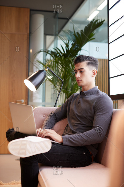 Young businessman sitting in modern casual office using laptop computer, side view