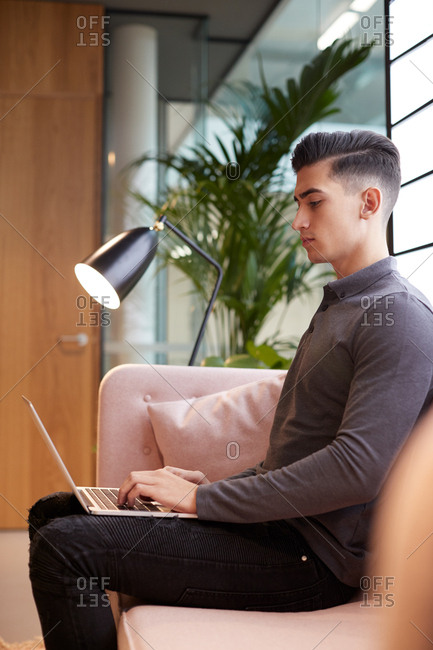 Young businessman sitting on sofa working with laptop on his knee, side view