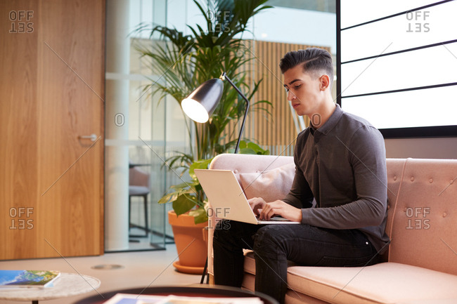 Young businessman sitting on sofa working with a laptop on his knee, side view