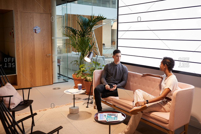 Young man and woman having an informal business meeting on a sofa in an office lounge